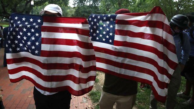 Personas detrás de banderas de Estados Unidos al aire libre