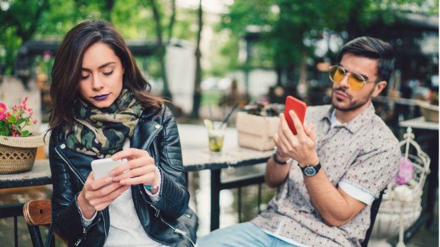 Pareja cada uno mirando su móvil