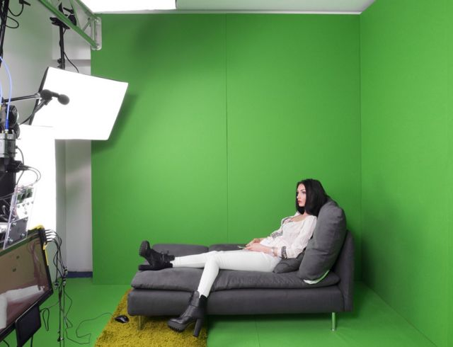 a model poses in a green-screen studio