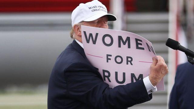 """Donald Trump con un cartel que dice """"Mujeres por Trump""""."""