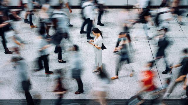 Persona revisando su teléfono en medio de varias personas caminando.