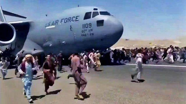 Cientos de afganos se lanzaron desesperados a la pista de despegue.