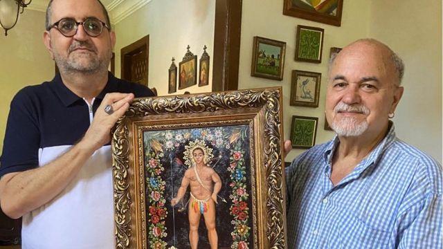 O historiador Sérgio Muricy e o antropólogo Luiz Mott com tela de São Tibira do Maranhão