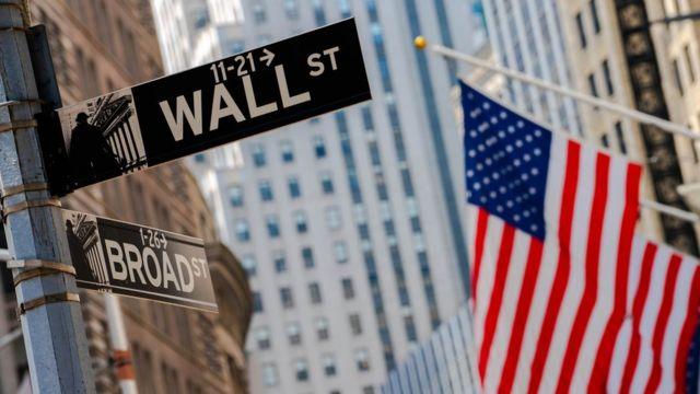 Placa de rua de Wall Street com bandeira americana ao lado