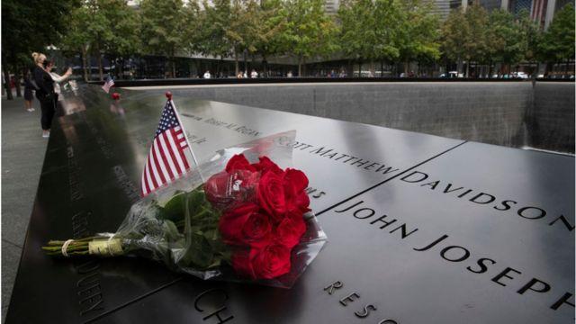 Một lá cờ Mỹ và hoa được đặt gần tên của một nạn nhân tại Đài tưởng niệm vụ 11/9 tại khu Ground Zero hôm 8/9/2021 ở New York, Hoa Kỳ