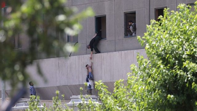 Iranian policemen try to help some civilians fleeing from the parliament building during an attack in Tehran, Iran, 07 June 2017
