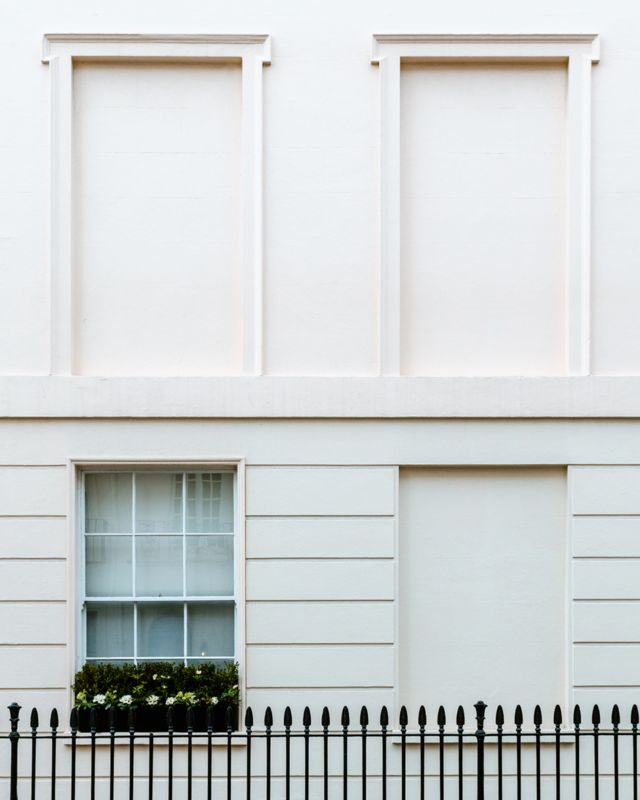 Three blocked windows and one unblocked window on a white building in South Eaton Place, London