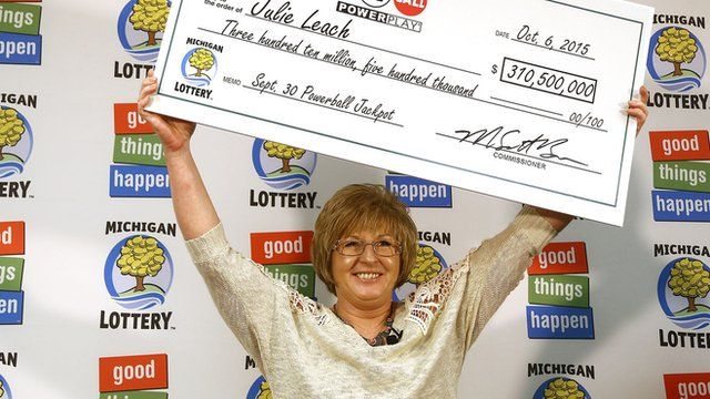 Julie Leach holds a cheque for $310.5 million above her head
