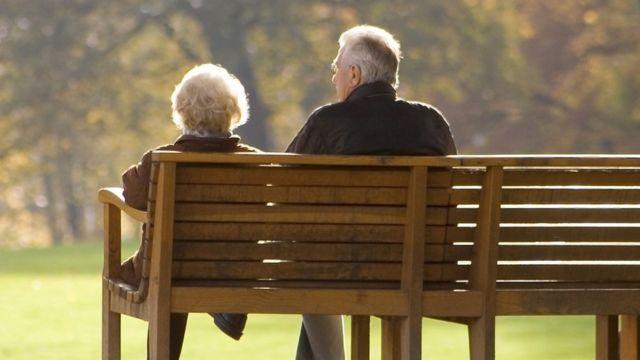Pareja de ancianos sentada en una banca