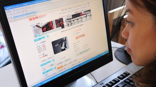 Mulher em frente ao computador pesquisa no site do Taobao