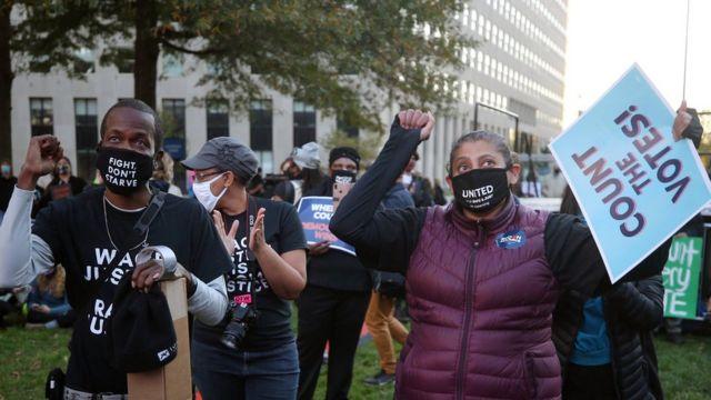 """Dos afroestadounidenses con carteles que rezan: """"¡Cuenten los votos!"""""""