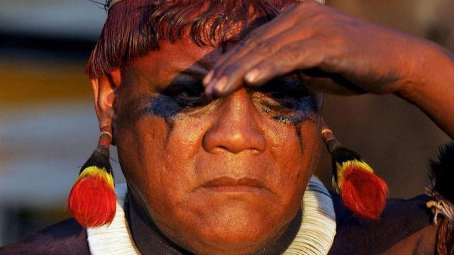 Close no rosto do líder indígena Aritana, que leva as mãos à testa para cobrir os olhos