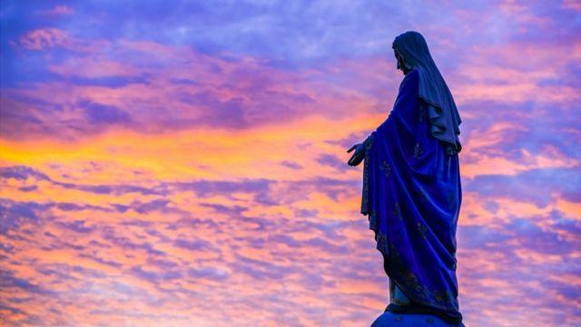Estátua de Nossa Senhora sob um céu multicolorido pelo por-do-dol