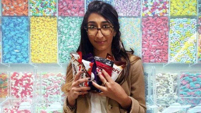 Radhika Sanghan em uma montagem segurando muitos doces