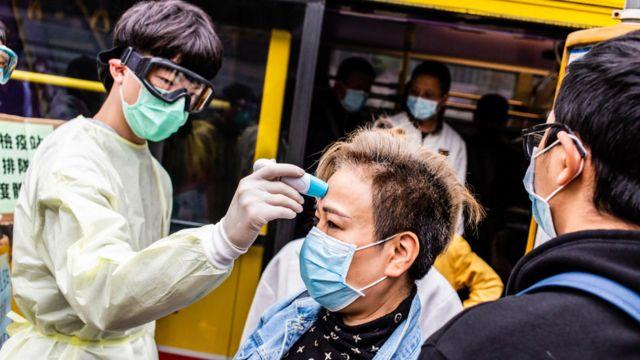 A volunteer measures a passenger's body temperature in Hong Kong