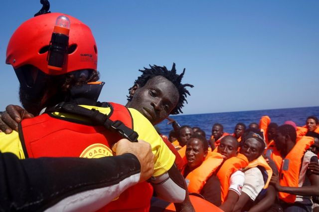 A migrant is carried from an overcrowded dinghy by a member of the Spanish NGO Proactiva off the Libyan coast