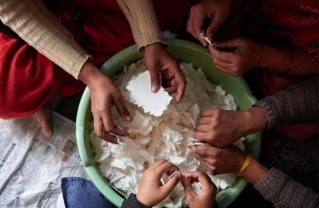 Las mujeres preparan el material para hacer compresas sanitarias.