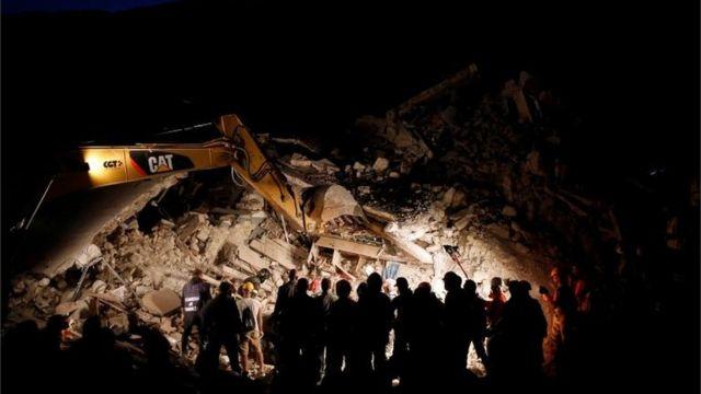 Rescatistas y máquinas excavadoras iluminadas en la noche.