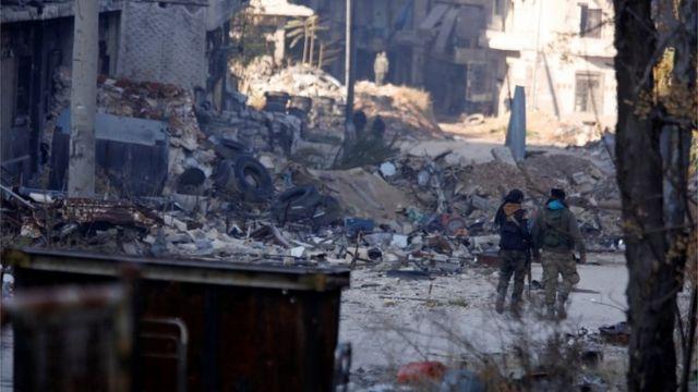 جنود من الجيش السوري يمشون وسط الأنقاض في حلب.