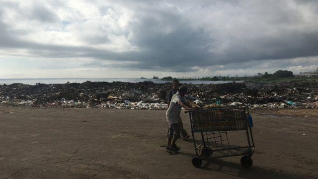 Pessoas caminham ao lado de lixão em Maracaibo, na Venezuela