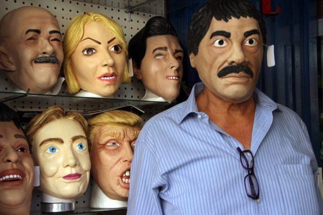 """Penjaga toko Manuel Robles (kanan) berpose dengan masker lateks yang menggambarkan penyelundup narkoba Meksiko, Joaquin Guzman Loera -alias """"El Chapo""""- yang dijual menjelang Hari Kematian di Ciudad Juarez, Negara Bagian Chihuahua, Meksiko, 25 Oktober"""