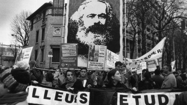 Foto de manifestantes en Francia en 1955 llevan un estandarte de Marx.