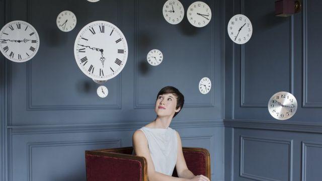 Mujer mirando varios relojes.