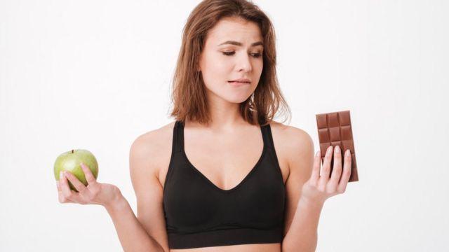Mujer entre una manzana y una tableta de chocolate.