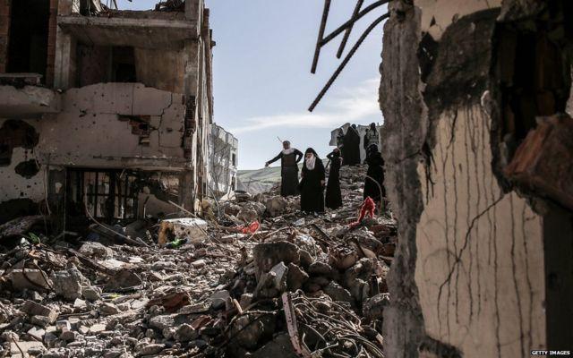 Люди у обломков своих домой на юго-востоке Турции