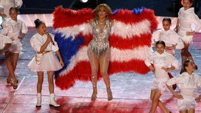 Jennifer López con la bandera de Puerto Rico y su hija.