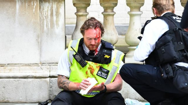 A police officer receives medical attention after police clashed with demonstrators in Whitehall