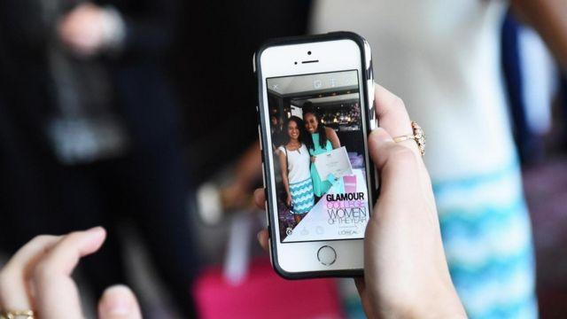 صورة على هاتف محمول لفتاتين، وتظر رسوم غرافيك في خلفيتها