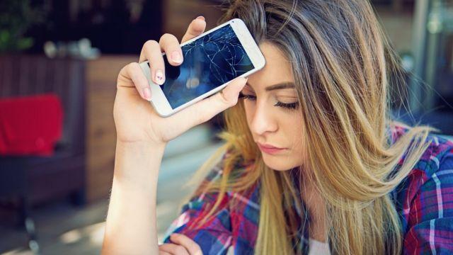 Joven con celular quebrado.