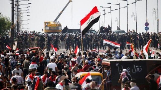 Демонстранты с флагами напротив полицейских сил