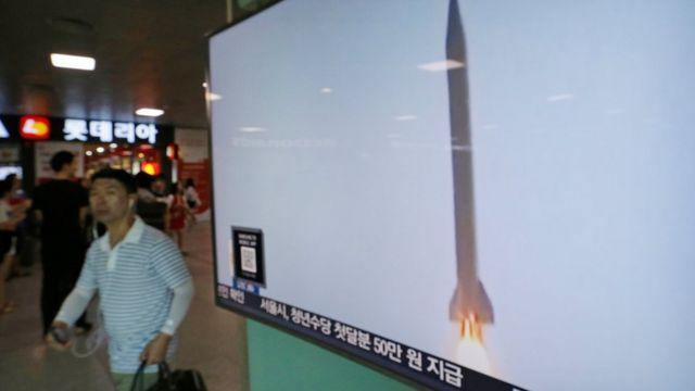 Un hombre pasa por una pantalla que muestra un misil