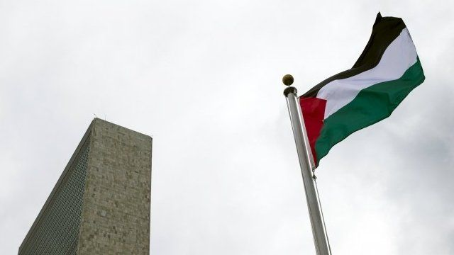 The Palestinian flag flies after being raised
