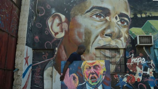 صورة أوباما على حائطة ويمر رجل يحمل صورة مرسومة لترامب