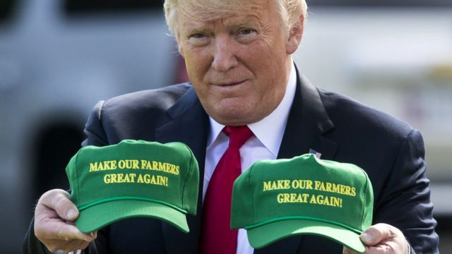 "US President Donald Trump displays hats that read: ""Make Our Farmers Great Again!"" at the White House, Washington DC, 30 August 2018"