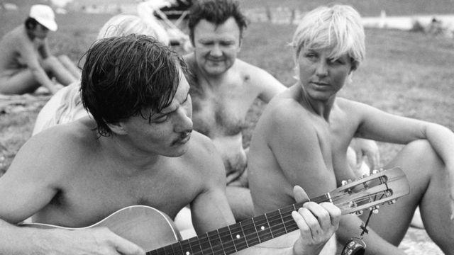 Grupo de pessoas nuas tocando violão