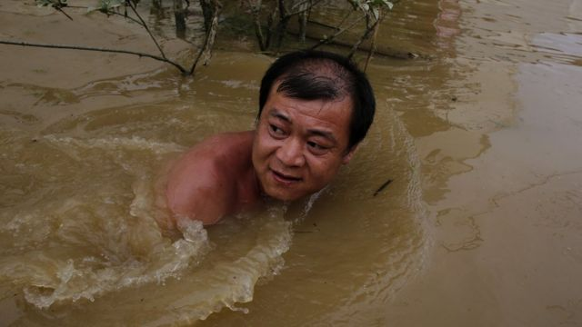 Villager swimming in floodwater in Wuhan