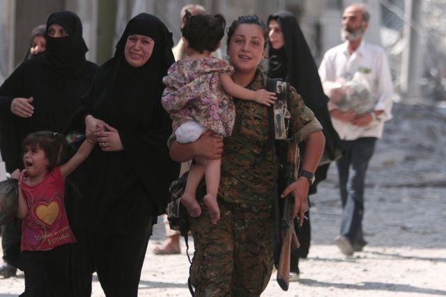 A fighter helps civilians who were evacuated an Islamic State-controlled neighbourhood of Manbij, Syria, 12 August