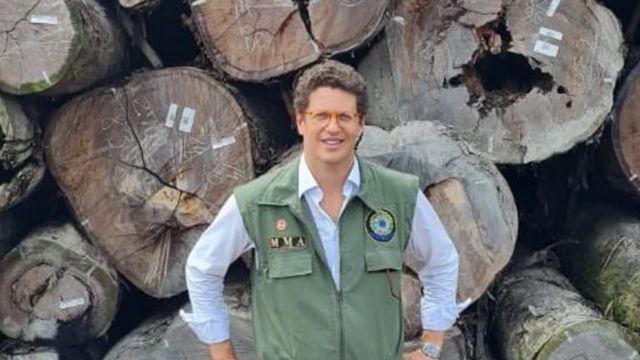 Ricardo Salles posa diante de madeira apreendida pelo Ibama