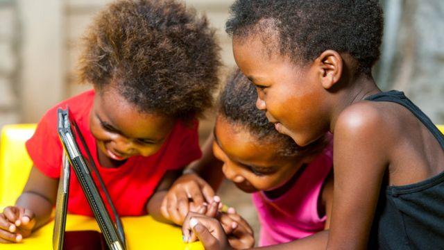 Três crianças assistindo a um tablet