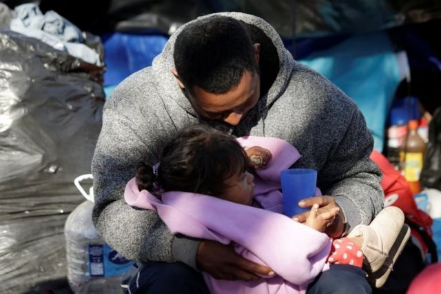 A Mexican man embraces his daughter near the Cordova-Americas international border bridge in Ciudad Juarez while waiting to apply for asylum to the US