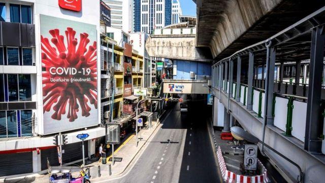 Màn ảnh khổng lồ công bố thông tin về virus corona COVID-19 trên một con đường vắng lặng ở trạm BTS Nana, một trong những khu vực du lịch đông đúc nhất của Bangkok vào ngày 26/3/2020