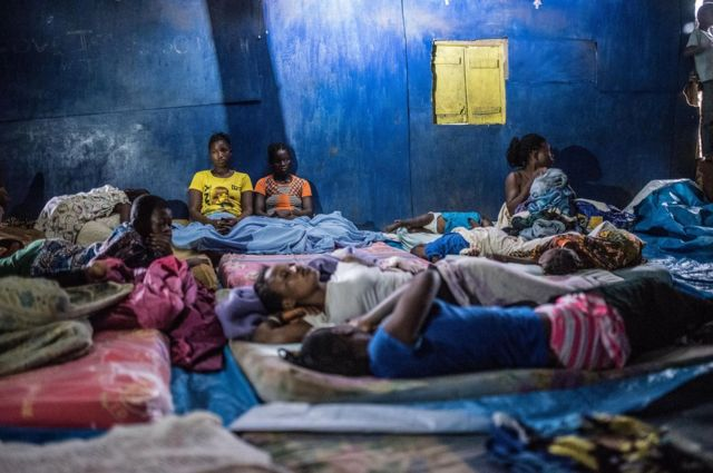 Women and children sleep on the floor of a church built from corrugated iron