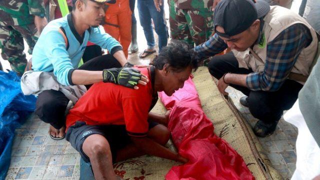 男子望着不幸在海啸中罹难的孩子