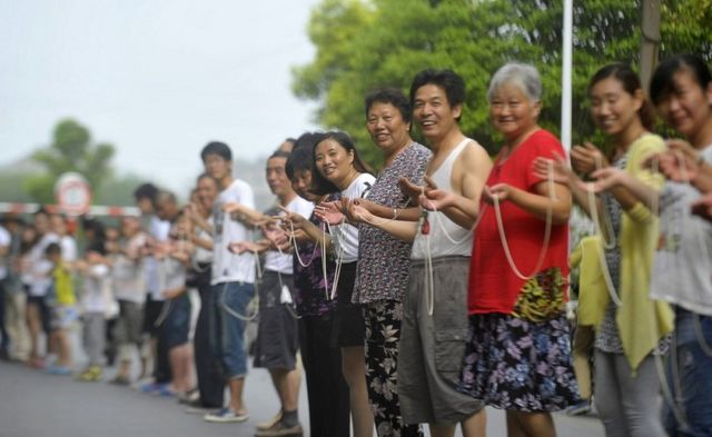 Residents show a 300-meter-long noodle made by students from Yangzhou University on July 23, 2015 in Yangzhou, Jiangsu Province of China.