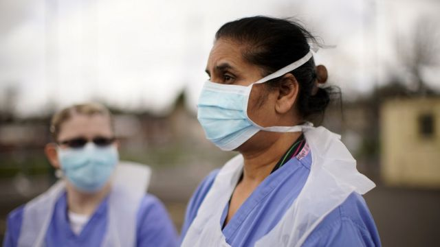 NHS nurses speak to the media as they wait for the next patient at a drive through Coronavirus testing site on March 12, 2020