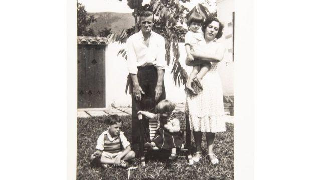 Foto em preto e branco mostra família no jardim